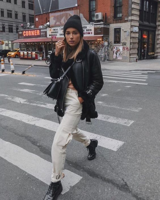 a winter look with white cargo pants, black boots, a black shearling coat, a beanie and a bag