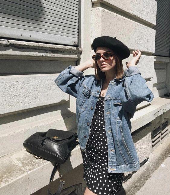 a black polka dot dress, an oversized denim jacket, a black beret, sunglasses and a black backpack