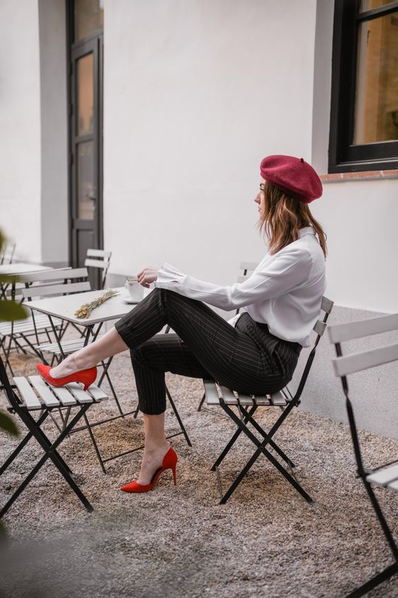 a fall office look with a white shirt, black striped pants, hot red shoes and a burgundy beret