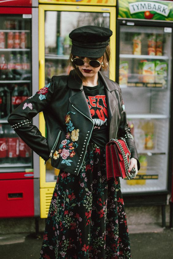 a black printed tee, a black floral midi skirt, a red bag and a black painted leather jacket plus a military cap