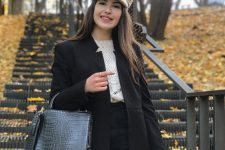 16 a white sweater, black high waised jeans, a black long blazer, a black bag and a neutral chain kepi