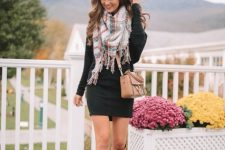 With black dress, beige high boots and leather bag