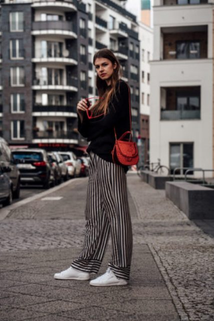 With black loose sweater, red bag, white sneakers and red framed sunglasses