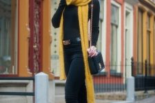 With black shirt, black pants, belt, yellow scarf and chain strap bag