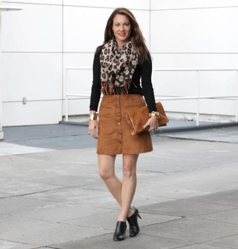 With black shirt, brown mini skirt, clutch and black boots