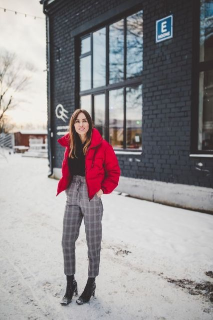 With black shirt, red puffer jacket and black ankle boots