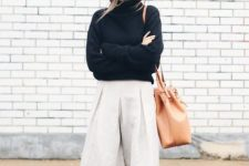 With black turtleneck, brown tote bag and black flat shoes