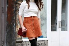 With brown suede mini skirt, black over the knee boots and chain strap bag