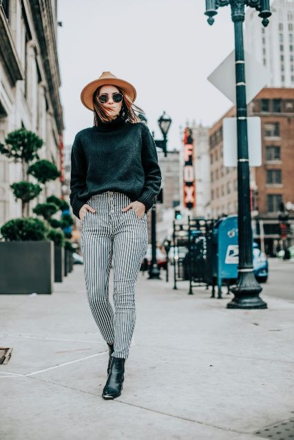 With emerald sweater, brown hat and black ankle boots