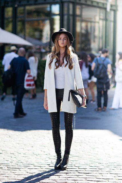 With gray shirt, black hat, black leather lace up pants, black clutch and leather boots