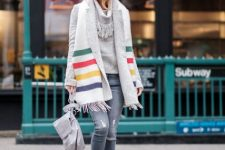 With gray sweater, gray coat, hat, gray bag, heeled boots and distressed jeans