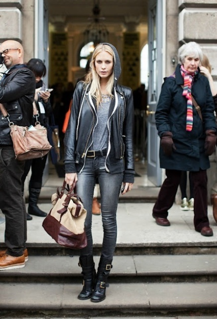 With gray t-shirt, black leather jacket, gray jeans and beige and brown bag