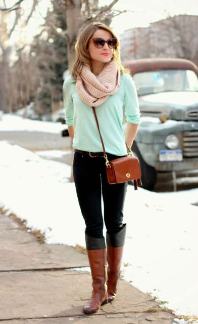 With mint green shirt, black pants, brown crossbody bag and brown and black high boots
