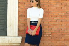 With navy blue pencil skirt, red clutch and white sneakers