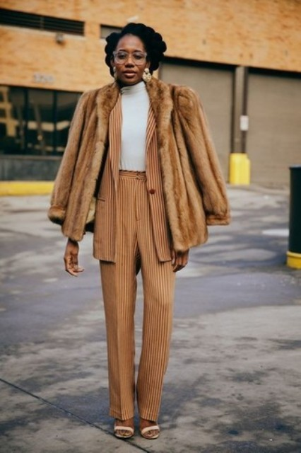 With striped blazer, fur jacket, white turtleneck and beige shoes