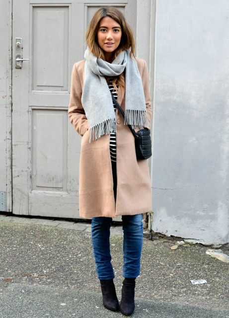 With striped shirt, beige coat, jeans, black bag and black ankle boots