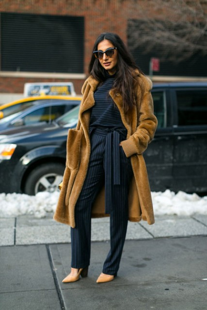 With striped shirt, brown fur coat and beige shoes