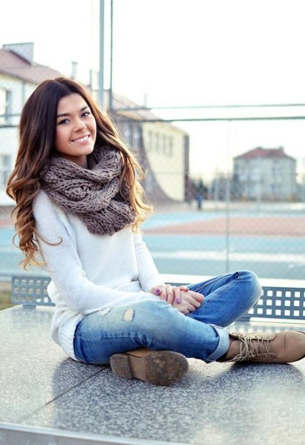 With white long sweater, distressed jeans and lace up boots