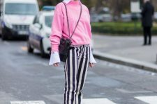 With white shirt, pink sweatshirt and black chain strap bag
