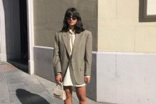 With white skirt, beige blouse, gray blazer and beige mini bag