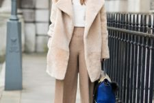 With white sweater, beige fur coat, printed pumps and bag