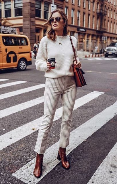 With white sweater, brown bag and brown leather mid calf boots