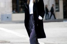 With white t-shirt, black knee-length coat and cutout boots