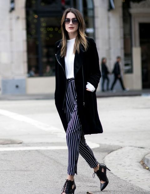 With white t shirt, black knee length coat and cutout boots