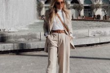 With white turtleneck, beige long blazer, crossbody bag and brown high boots