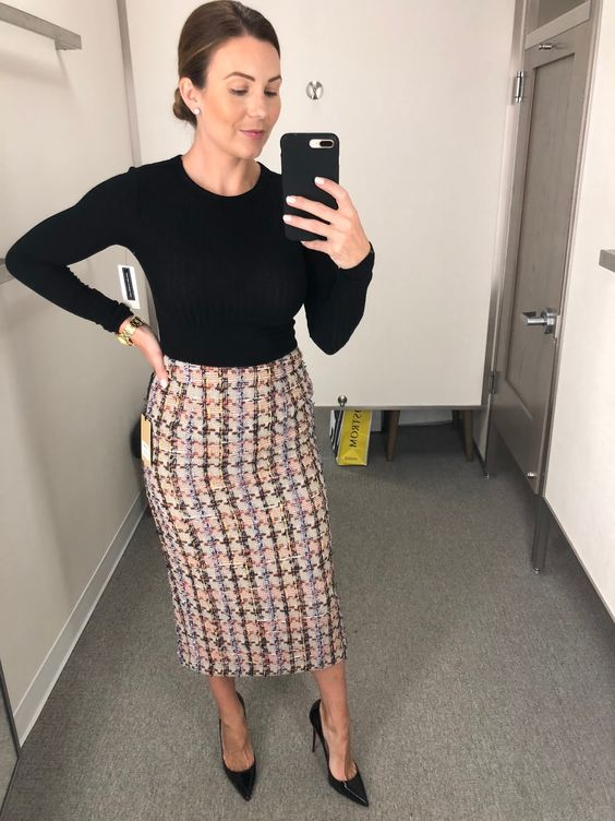 a black long sleeve top, a tweed midi skirt, black shoes for a stylish work look