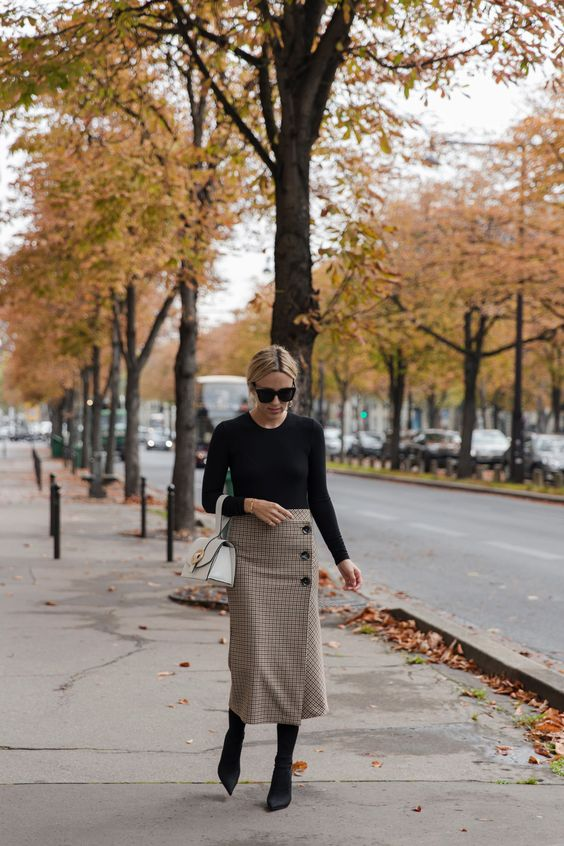 a black long sleeve top, a tweed skirt on buttons, black sock boots and a white bag for fall