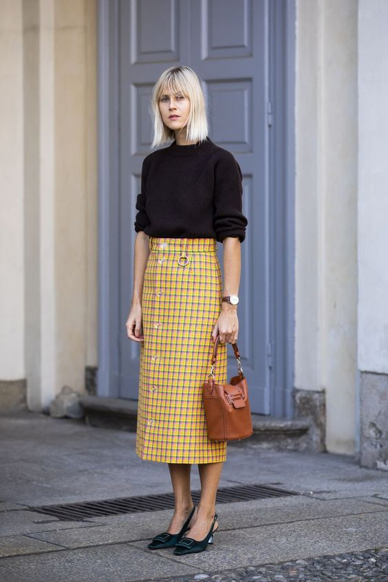 a black long sleeve top, a yellow tweed midi skirt on buttons, black slingbacks and a brown bag