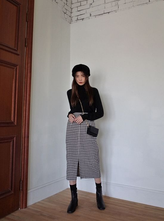 a black turtleneck, a black beret, bag and boots plus a monochromatic midi skirt of tweed