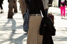 a black turtleneck, a tweed midi skirt with a front slit, black shoes and tights plus a black coat