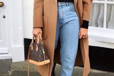 a black turtleneck, blue jeans, black combat boots, a brown midi coat, a printed bag