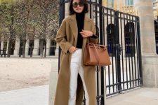 a black turtleneck, white jeans, black sock boots, a mustard midi coat, a brown bag
