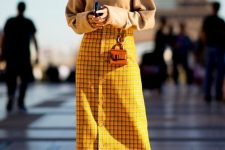a camel sweater, a bright yellow midi skirt on buttons, matching boots and a tiny bag for a bold look
