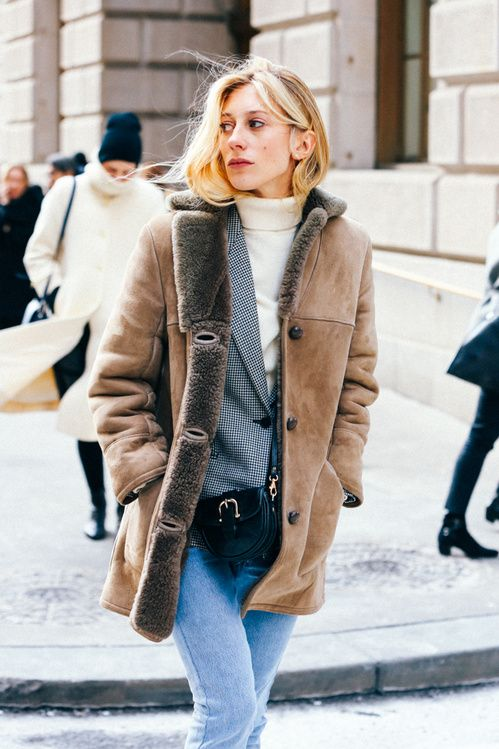 a chic winter look with a white turtleneck, blue jeans, a plaid blazer, a tan shearling coat and a bag