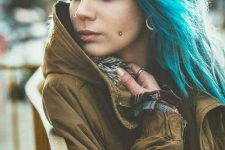 a double cheek piercing, a lip piercing and tunnel piercings plus blue hair for a super bold look