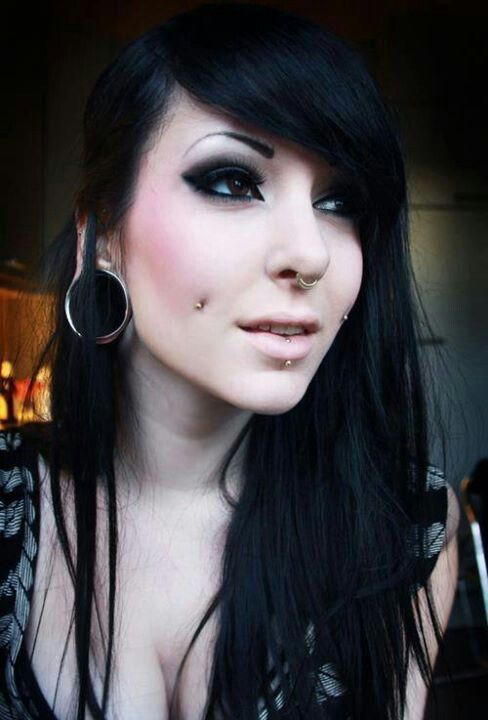 a double cheek piercing, a septum and a lip piercing with matching jewelry plus large tunnels