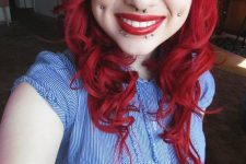 a double cheek piercing, a septum and lip piercing plus red hair to rock a very bold look