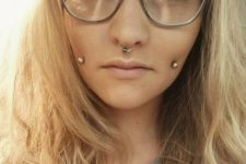 a double cheek piercing and a septum one spice up the nerdy look making it edgy and bolder