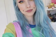 a double cheek piercing and tunnel piercings and blue hair for a super bold modern look