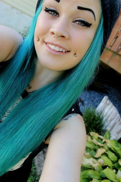 a double cheek piercing plus a septum one and blue hair for an extra bold look that stands out