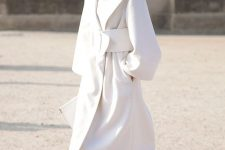 a gorgeous white midi coat, white laser cut shoes, a white clutch and a sculptural belt for a statement