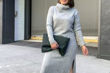 a grey fitting sweater dress with side slits, white sneakers and a black oversized clutch