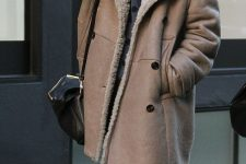 a grey top with polka dots, blue jeans, a brown shearling coat with faux fur and a black bag