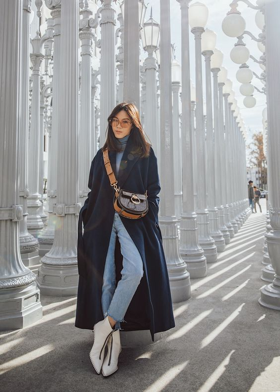 a light blue turtleneck, matching jeans, white boots with zips, a teal midi coat and a printed bag