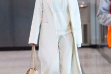 a monochromatic outfit in white, with a hoodie, pants, a midi coat and a tan bag