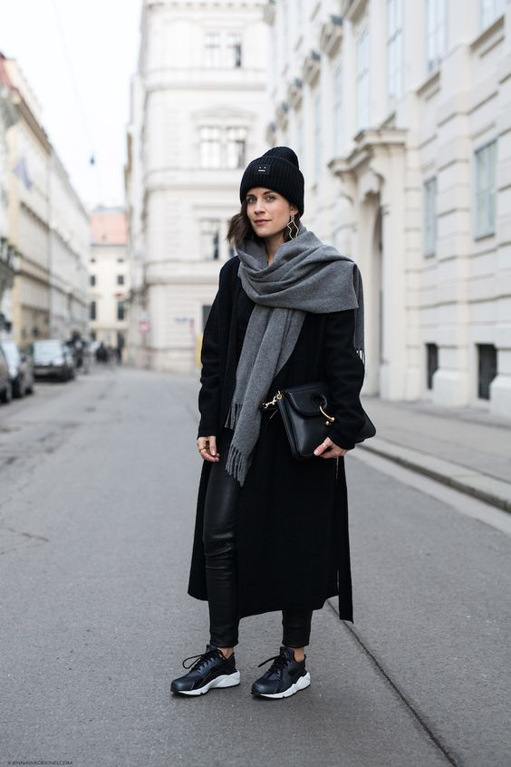 a monochromatic outfit with black leather leggings, trainers, a midi coat, a bag, a beanie and a grey scarf